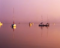 Brilliant sunrise. Cutting through the morning fog with sailboats at their moorings Royalty Free Stock Photography