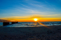 Brilliant sunrise over the waters of Lake Huron. Sunrise over the waters of Lake Huron in Oscoda Michigan at the beach park pier Stock Photos
