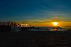 Brilliant sunrise over the waters of Lake Huron. Sunrise over the waters of Lake Huron in Oscoda Michigan at the Oscoda beach park pier Stock Photo