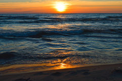 Brilliant sunrise over the waters of Lake Huron. Sunrise over the waters of Lake Huron in Oscoda Michigan at the Oscoda Beach Pier Stock Image