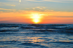 Brilliant sunrise over the waters of Lake Huron. Sunrise over the waters of Lake Huron in Oscoda Michigan at the Oscoda Beach Pier Royalty Free Stock Image
