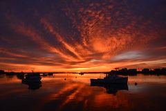 Brilliant Sunrise reflected on New England harbor. Orange sunrise illuminates New England morning; Dramatic sunrise lights up the sky in New Hampshire; Majestic stock photography