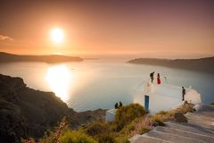 Brilliant sunset at Fira with a church and a bride on a roof, Santorini, Stock Photography