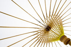 Brilliant white tropical umbrella. Conjuring up the feeling of summer and holidays, a tropical beach umbrella or parasol silhoutted against the white sky Royalty Free Stock Image