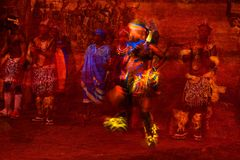 Brilliantly colored African Dancer Abstract in Motion and people in Native costume against a textured red background. Brilliantly colored African Dancer Abstract Stock Photography