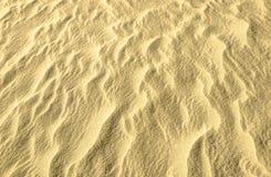 Brillo de oro en fondo de la arena fotografía de archivo libre de regalías