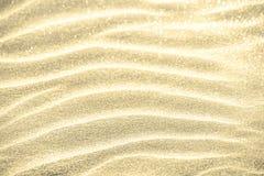 Brillo de oro en fondo de la arena foto de archivo