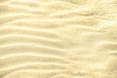Brillo de oro en fondo de la arena imagen de archivo libre de regalías