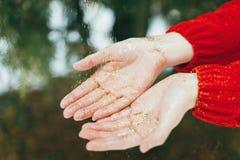 Brillo de oro en manos Imagenes de archivo