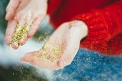 Brillo de oro en manos Fotos de archivo libres de regalías