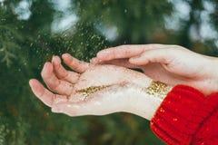 Brillo de oro en manos Fotografía de archivo libre de regalías