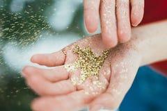Brillo de oro en manos Fotos de archivo