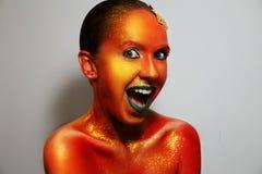 Brillo del cuerpo Emociones femeninas, buen humor Arte de cuerpo Arte de la cara Fondo gris Aislado cosméticos, máscara facial di Imagenes de archivo