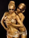 Brillo. Esmalte. Mujeres atractivas con el abrazo de oro de los cuerpos. Fantasía Imágenes de archivo libres de regalías