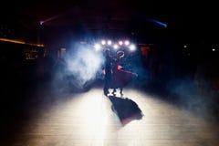 Brillo ligero azul sobre el baile de los pares de la boda en la oscuridad foto de archivo libre de regalías
