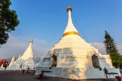 Brillo ligero de oro en blanco y pagoda del oro durante salida del sol/puesta del sol con el cielo azul Imagenes de archivo