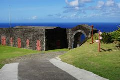 Brimstone Hill Fortress entrance gate and road with directions sign, St. Kitts Island Royalty Free Stock Photo