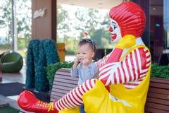Brincadeira asiática pequena bonito feliz do menino da criança com Ronald McDonald imagem de stock