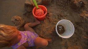 A brincadeira com bola e a cubeta sentam-se na areia filme