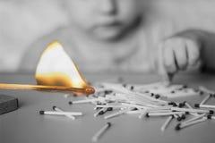 Brincadeiras com fósforos no primeiro plano um fósforo ardente, uma criança e fósforos, um fogo, perigoso, preto e branco foto de stock royalty free