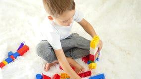 Brincadeiras com os blocos da cor que sentam-se em um fundo branco O menino feliz está jogando O conceito do desenvolvimento infa video estoque