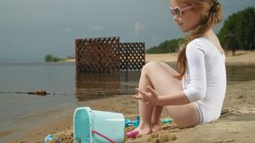 Brincadeiras da menina com a areia na praia usando estatuetas dos moldes Dia de ver?o ensolarado f?rias video estoque