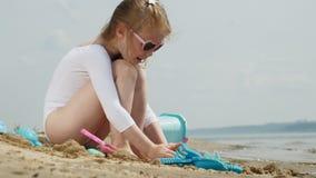 Brincadeiras da menina com a areia na praia usando estatuetas dos moldes Dia de ver?o ensolarado f?rias vídeos de arquivo