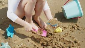 Brincadeiras da menina com a areia na praia usando estatuetas dos moldes Dia de ver?o ensolarado f?rias filme