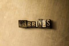 BRINCOS - close-up vintage sujo da palavra typeset no contexto do metal Imagens de Stock