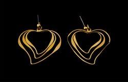 Brincos folheados a ouro em um fundo preto Fotografia de Stock Royalty Free