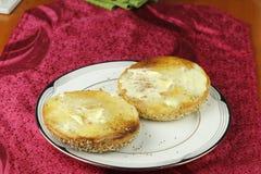 Brindado e posto manteiga tudo Bagel em uma placa Imagens de Stock