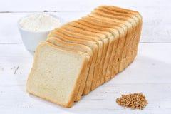 Brinde as fatias da fatia do pão cortadas na placa de madeira imagem de stock