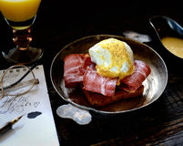Brinde com bacon e ovo escalfado em uma frigideira em um fundo de madeira escuro Imagens de Stock