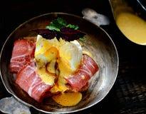 Brinde com bacon e ovo escalfado em uma frigideira em um fundo escuro Imagens de Stock