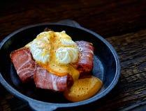 Brinde com bacon e ovo escalfado em uma frigideira em um fundo escuro Imagem de Stock