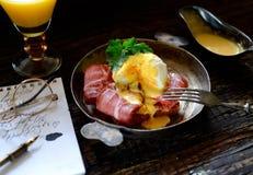 Brinde com bacon e ovo escalfado em uma frigideira, forquilha do vintage em um fundo escuro Imagens de Stock Royalty Free