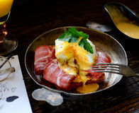 Brinde com bacon e ovo escalfado em uma frigideira, forquilha do vintage em um fundo escuro Fotos de Stock