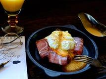 Brinde com bacon e ovo escalfado em uma frigideira, forquilha do vintage em um fundo escuro Fotografia de Stock Royalty Free