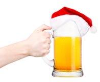 Brinde com cerveja e chapéu de Santa Imagens de Stock Royalty Free