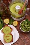 Brinde com pasta do feijão e as favas fervidas no fundo de madeira Imagens de Stock
