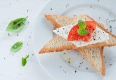 Brinde com requeijão, fatia do tomate e manjericão fresca Imagens de Stock