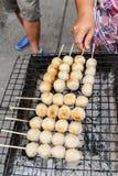 Brinde da almôndega da carne de porco da grade do vendedor na grade Fotografia de Stock