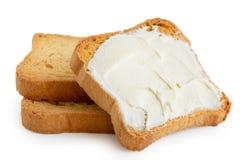 Brinde de Melba com o queijo creme que encontra-se em dois brindes lisos isolados imagem de stock