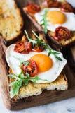 Brinde do café da manhã com ovo, os tomates roasted e a salada da rúcula Imagem de Stock Royalty Free