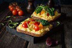 Brinde do café da manhã: pão, ovos mexidos, queijo e tomate brindados foto de stock
