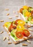 Brinde do pão do risp do ¡ de Ð com queijo creme, abacate fresco, cereja tom fotografia de stock royalty free