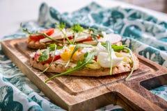 Brinde dobro com ovo, aragula, tomate e queijo, pão da rabanada com vegetarianos Fotos de Stock Royalty Free
