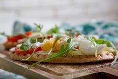 Brinde dobro com ovo, aragula, tomate e queijo, pão da rabanada com vegetarianos Imagens de Stock