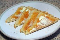 Brinde e manteiga em uma placa para o café da manhã Foto de Stock