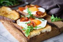 Brinde saudável do café da manhã com ovo, o tomate roasted e a rúcula na placa de corte de madeira rústica Fotos de Stock